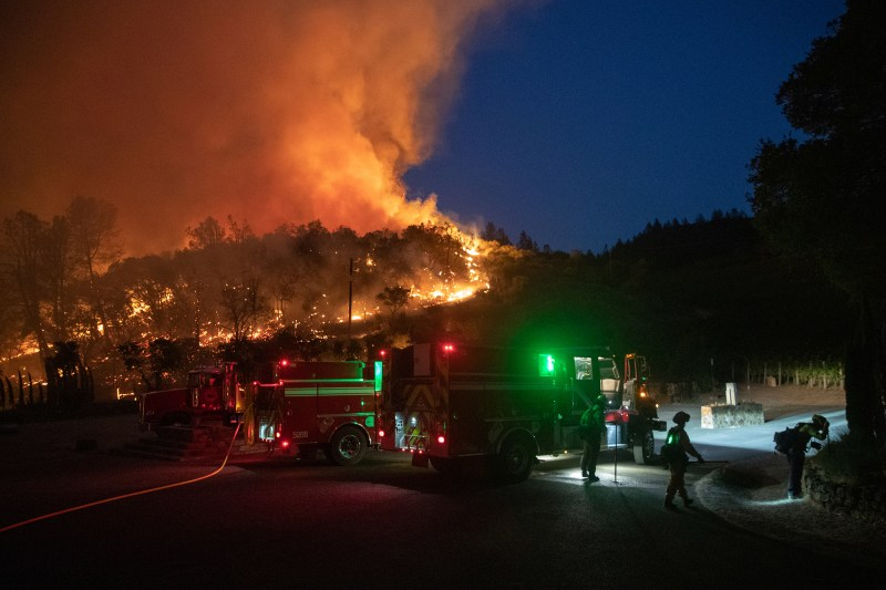 Firefighters protect a residence from the Glass Fire at a vineyard in Deer Park, California