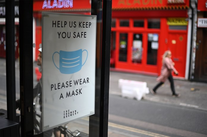 A sign advising people to wear a face mask is shown on the door of a business in London