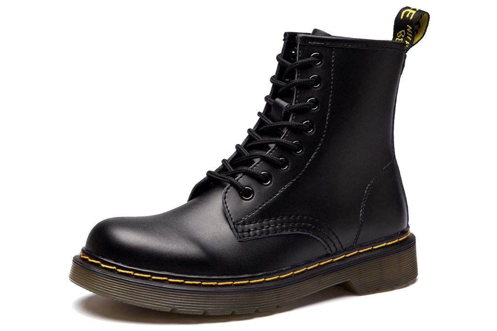 A black combat boot with yellow trim and tag on the back