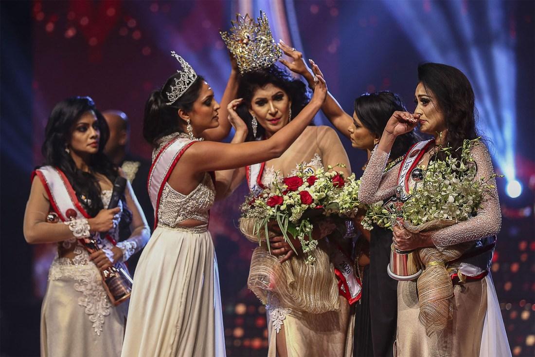 Mrs. Sri Lanka 2020 Caroline Jurie (left) removes the crown of 2021 winner Pushpika de Silva (center) as she is disqualified