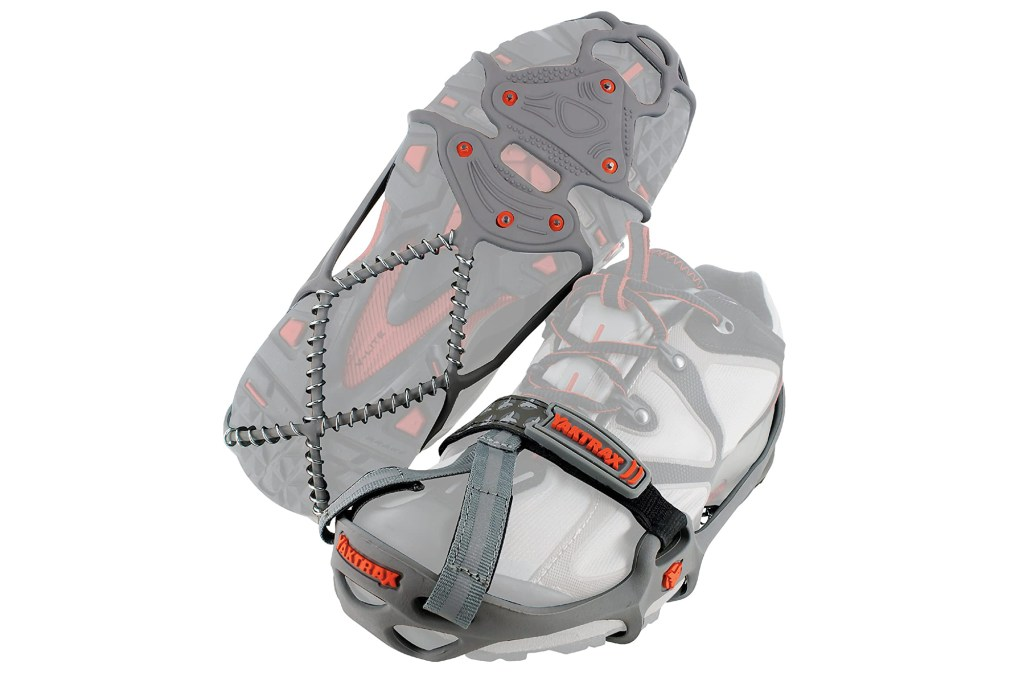 A pair of shoes showing hiking spike attachments on a gray chain