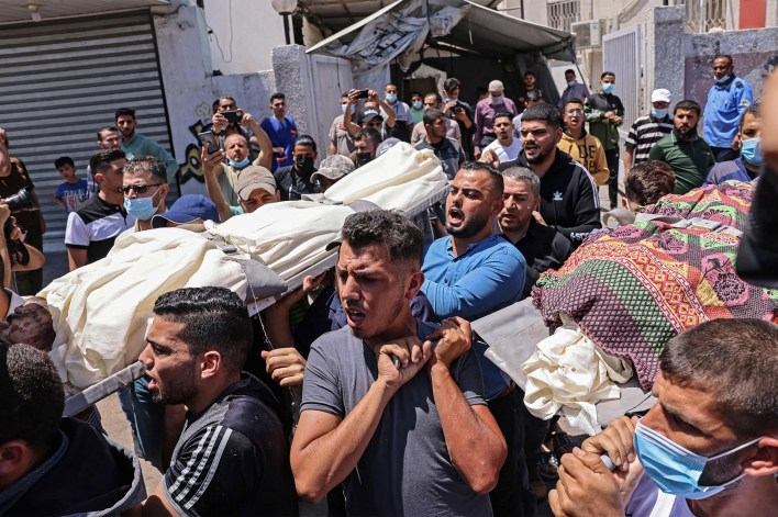Palestinians carry the dead body of Raed Alrantisi, who was killed in an Israeli air strike, during his funeral in the southern Gaza Strip on May 14, 2021.