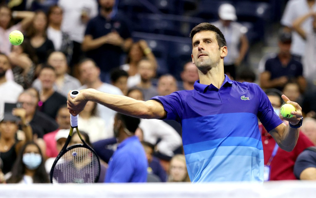 Novak Djokovic hits an autographed ball into the crowd after his first-round victory over Holger Rune.