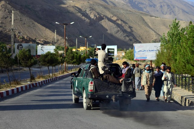 Afghan security forces patrol along a road on a pickup vehicle in Bazarak town of Panjshir province on August 17, 2021.