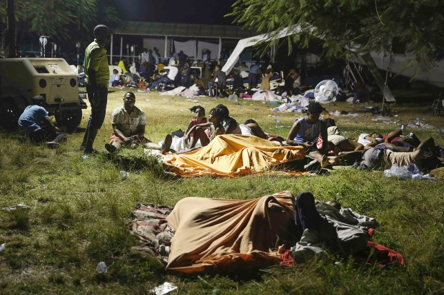 People displaced by their earthquake-damaged homes spend the night outside in a grassy area that is part of a hospital in Les Keys on Saturday, August 14, 2021.  A magnitude 7.2 earthquake shook southwestern Haiti on Saturday.