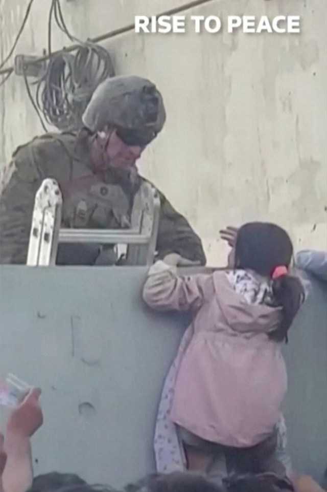 A U.S. soldier stands guard while a girl tries to climb over a wall near the Kabul airport.
