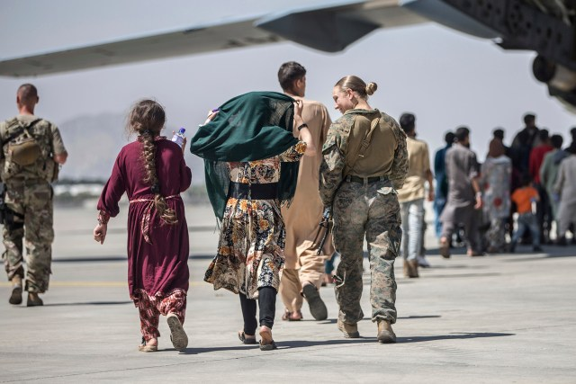 Sgt. Nicole Gee walks with a family during ongoing evacuations at Hamid Karzai International Airport, Kabul, Afghanistan on Aug. 24, 2021.