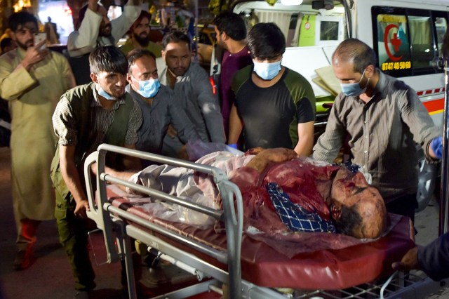 Volunteers and medical staff bring an injured man for treatment after two explosions killed at least six people outside the airport in Kabul on August 26, 2021.