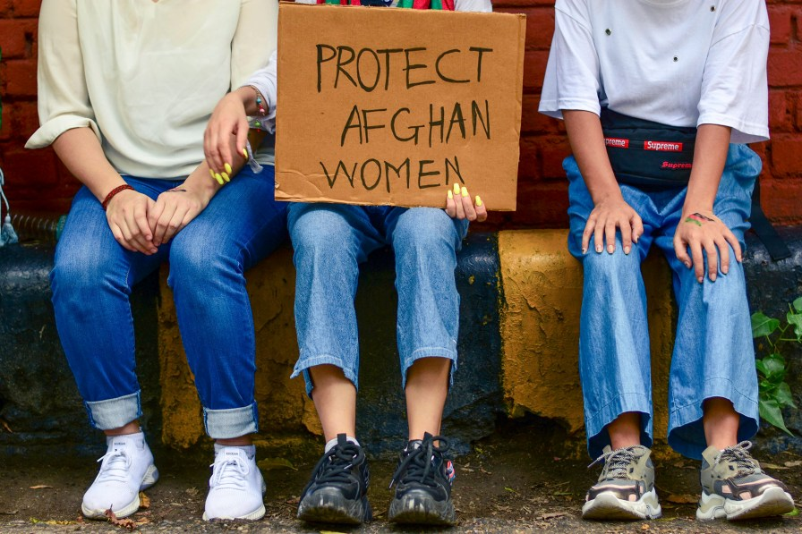 An Afghan refugee has a poster during a demonstration against the Taliban in New Delhi.