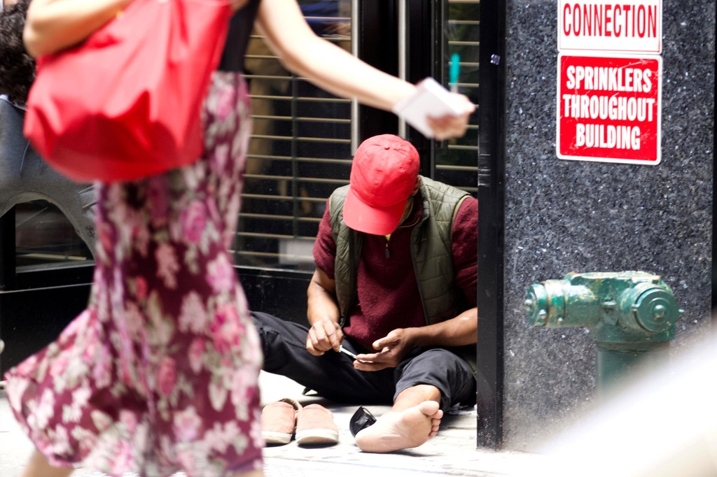 Two men taking some form of narcotics in a needle for their high on West 35th Street near 8th Avenue in Manhattan