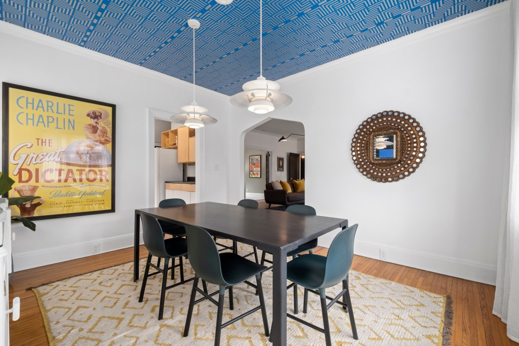Off to the side of the living area is a dining room with a prominent patterned ceiling.