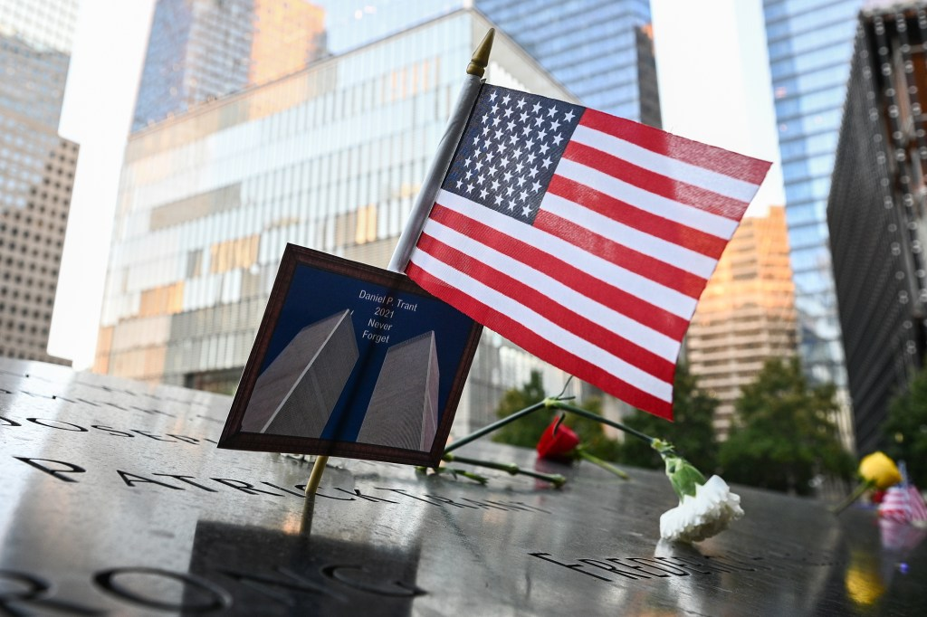 An American flag is placed along with a photo of the Twin Towers at the name of Daniel P. Trant at the 9/11 memorial.