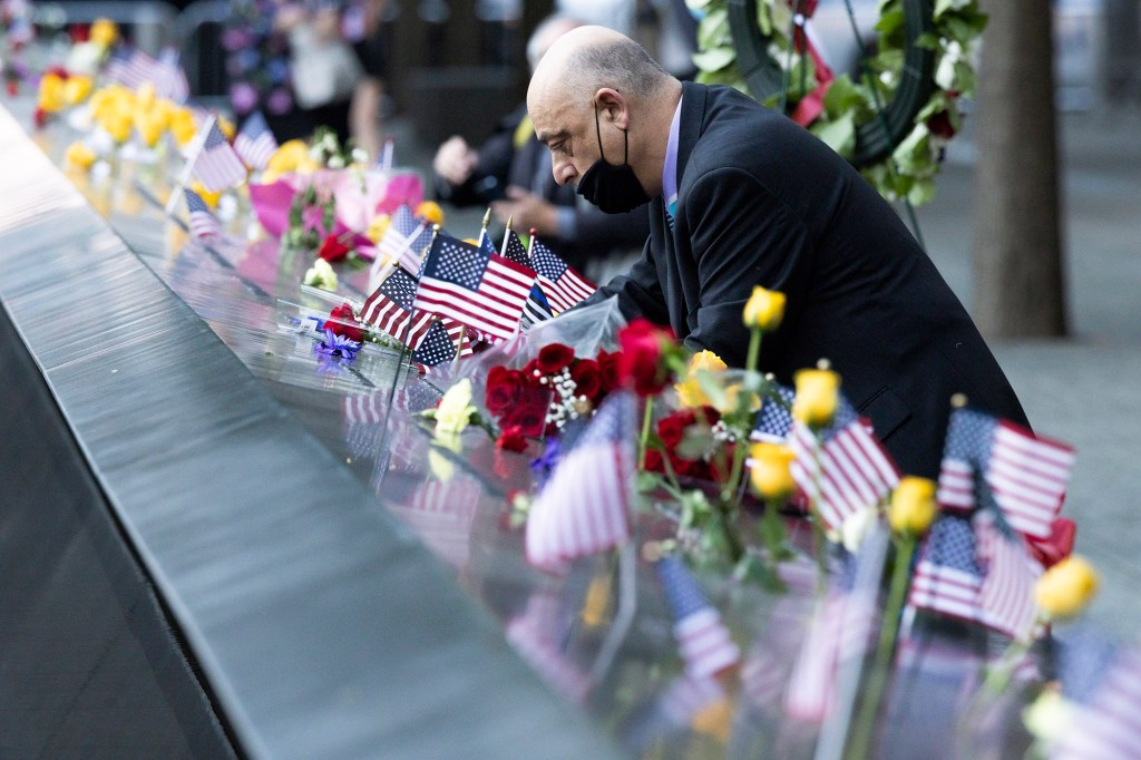A man places American flags on the South Pool of the 9/11 Memorial.