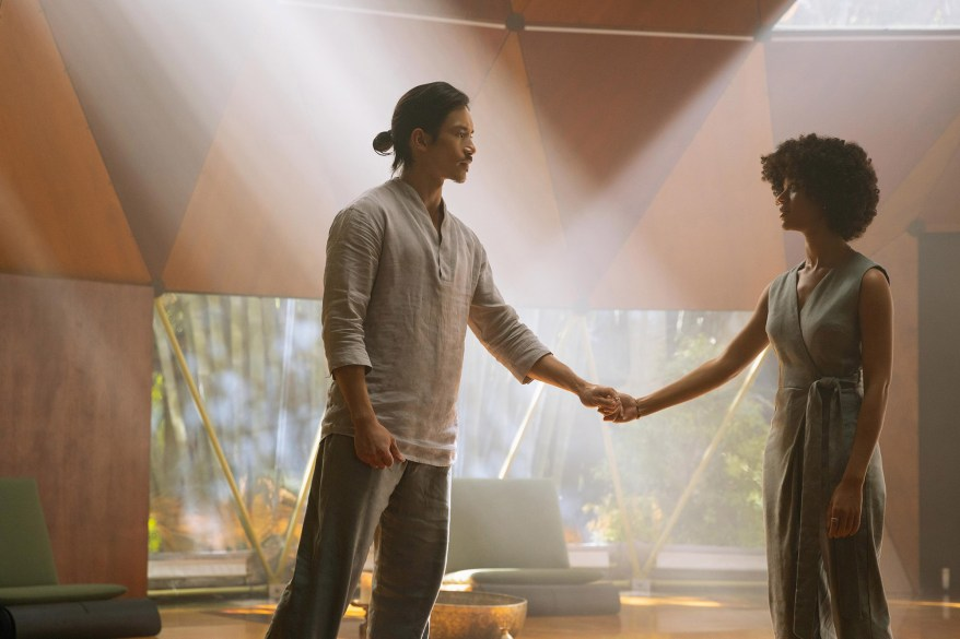 Manny Jacinto, playing Tao, steps into a beam of light in the yoga dome.