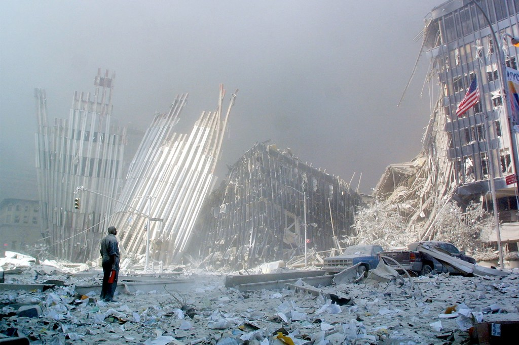 A man standing by the debris at Ground Zero after the towers collapsed on 9/11.