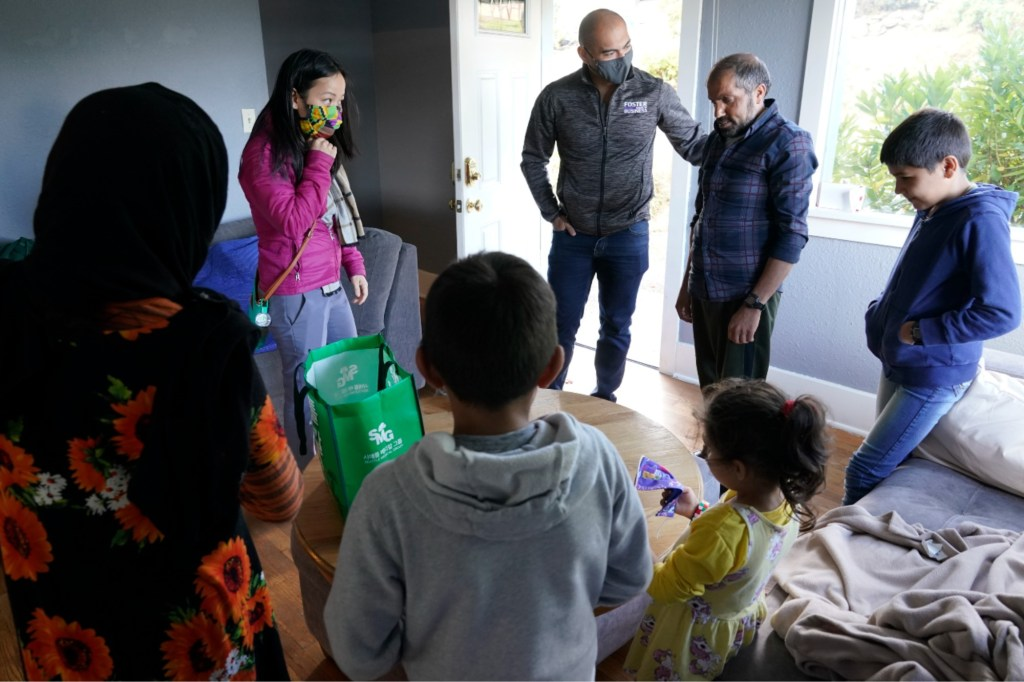 Do and her husband center, talk with Abdul and his family to drop off produce from their garden and check on the family.