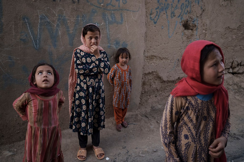 Afghan girls look up and listen as a neighbour describes when two men fell from a U.S. Air Force C-17 taking off from Kabul's International Airport on Aug. 16 and landed on the rooftop of his house in Kabul, Afghanistan, Friday, Sept. 17, 2021.