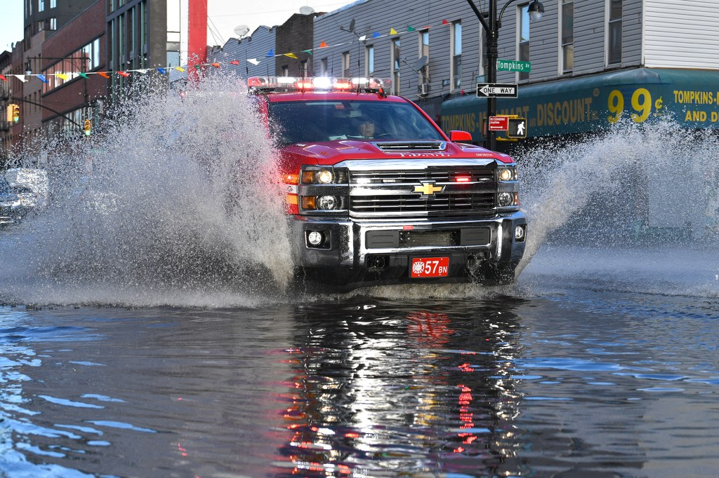 Truck drives through flooded street.