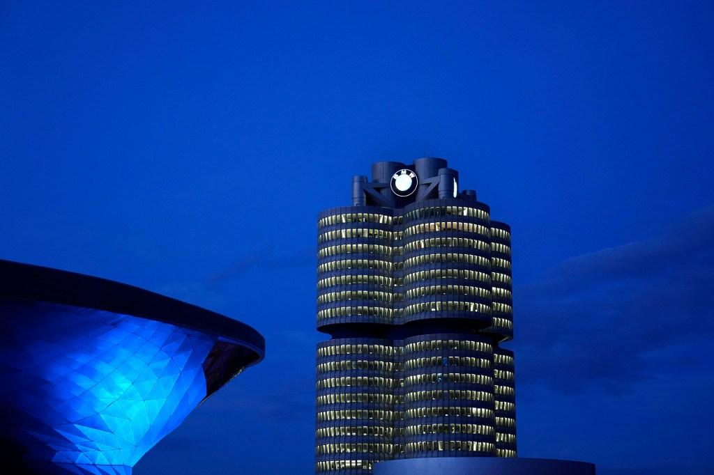 In this May 22, 2021 file photo the headquarters of German car manufacturer BMW is illuminated in Munich, Germany.
