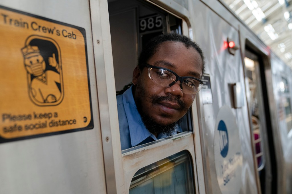 Desmond Hill, a vaccinated MTA conductor, checks the platform for late riders attempting to board the train
