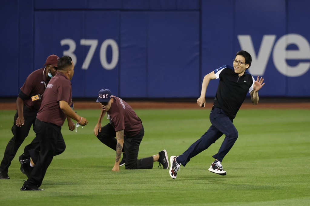 The fan gives his best effort to elude Citi Field security.