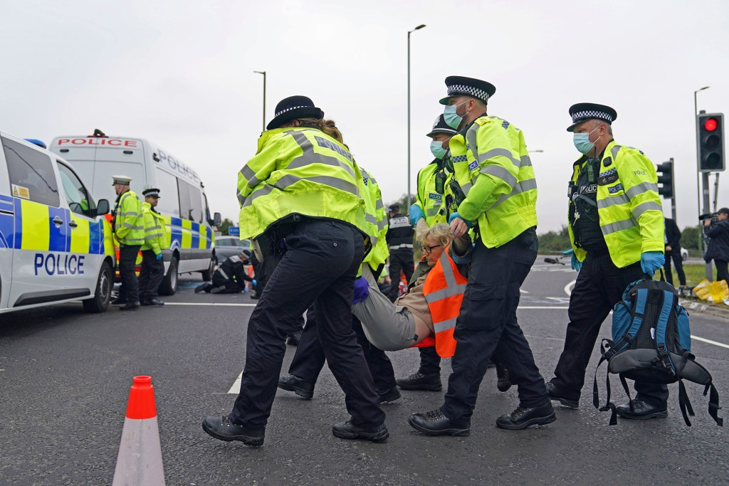 Police officers carry away one of a number of protesters who had glued themselves to the highway at a slip road at Junction 4 of the A1(M), near Hatfield, England, Monday Sept. 20, 2021.