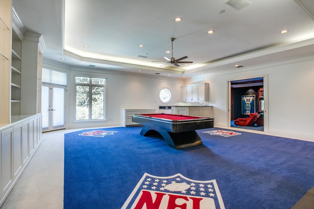 The NFL-themed billiards room is decked out with a lighted trey ceiling, an NFL carpet and an oculus window.