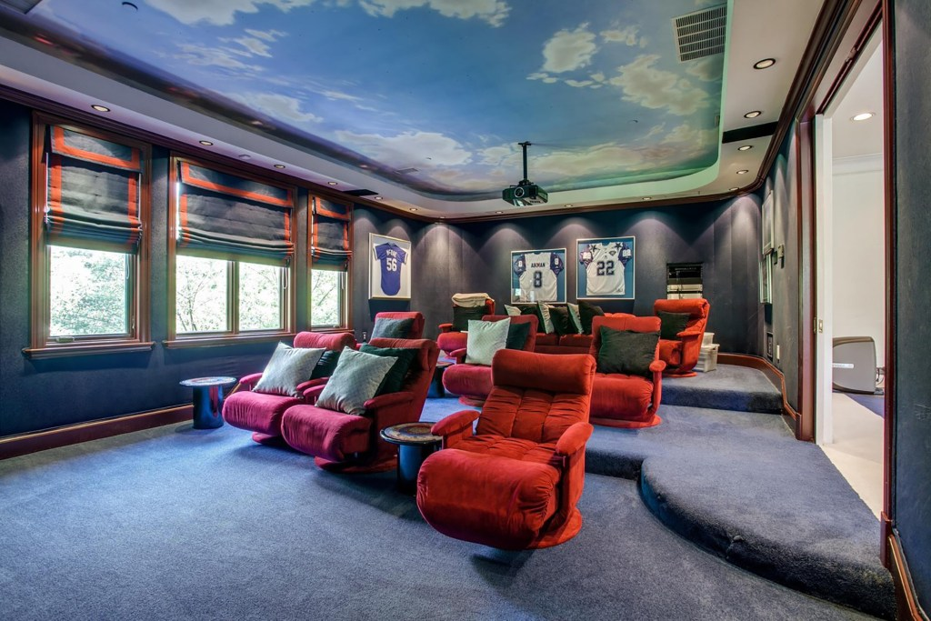 The 11-seat projector-based media room has red velvet chairs and a cloudy-sky mural ceiling painting.