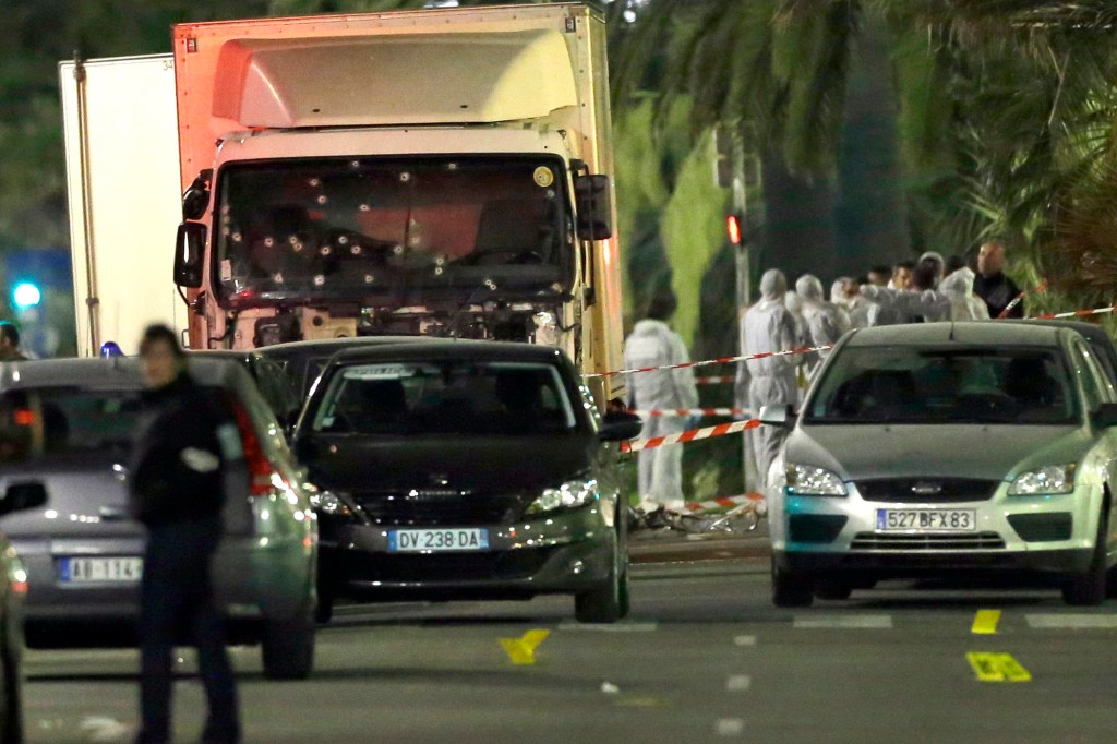 In this July 15, 2016 file photo forensic officers stand near a truck with its windscreen riddled with bullets, that plowed through a crowd of revelers who'd gathered to watch the fireworks in the French resort city of Nice, southern France.