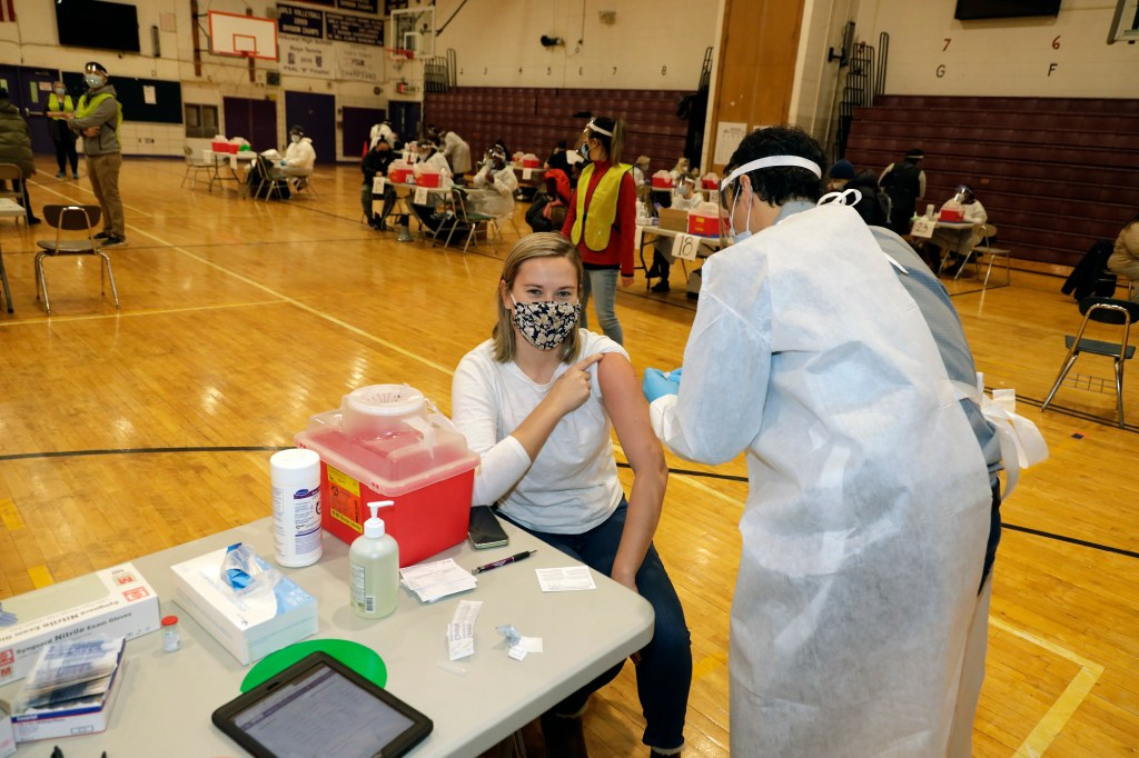 Carly Collins, 29 (R), physical therapist in the South Bronx receiving her COVID-19 vaccination.