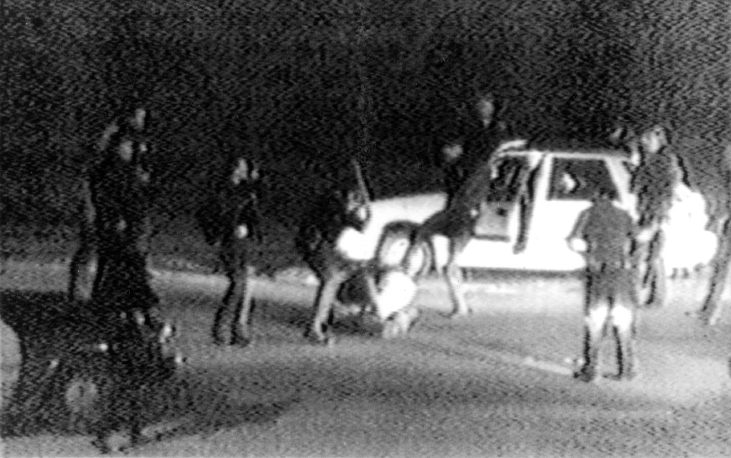 A still from a video tape shot by George Holliday from his apartment in a suburb of Los Angeles shows what appears to be a group of police officers beating a man with nightsticks and kicking him as other officers look on.