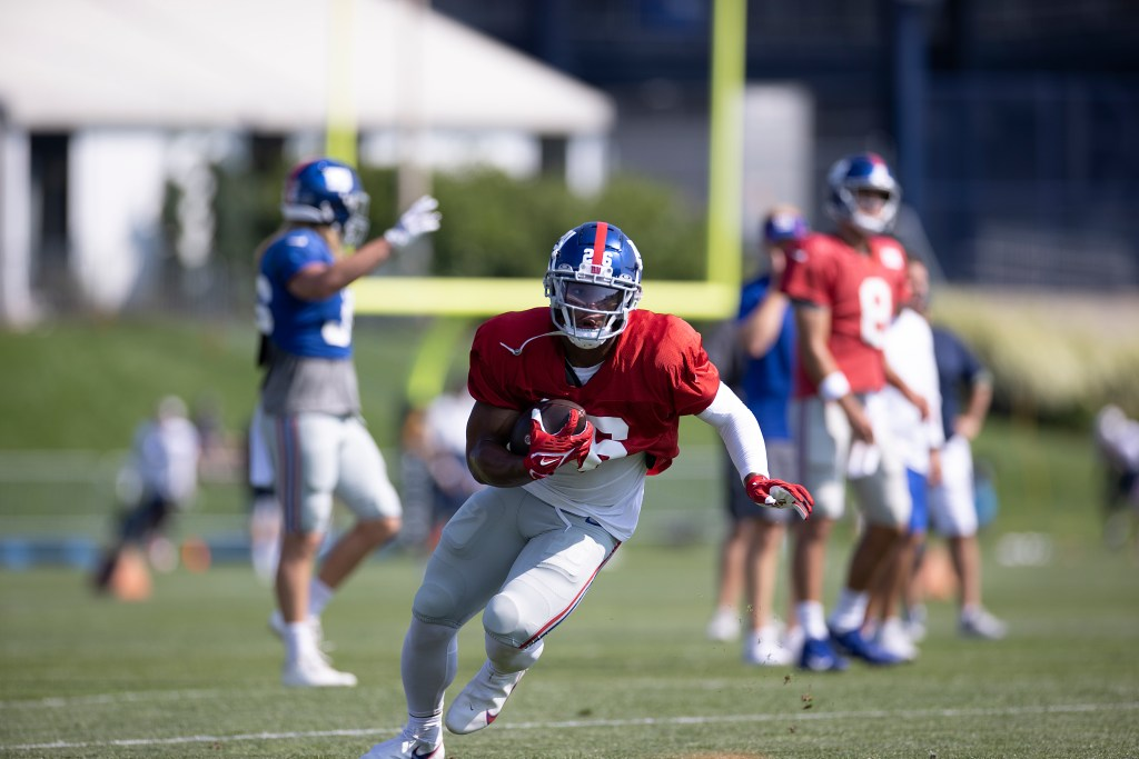 Saquon Barkley runs with the ball during the Giants' practice with the Patriots in Foxborough on Aug. 25, 2021.