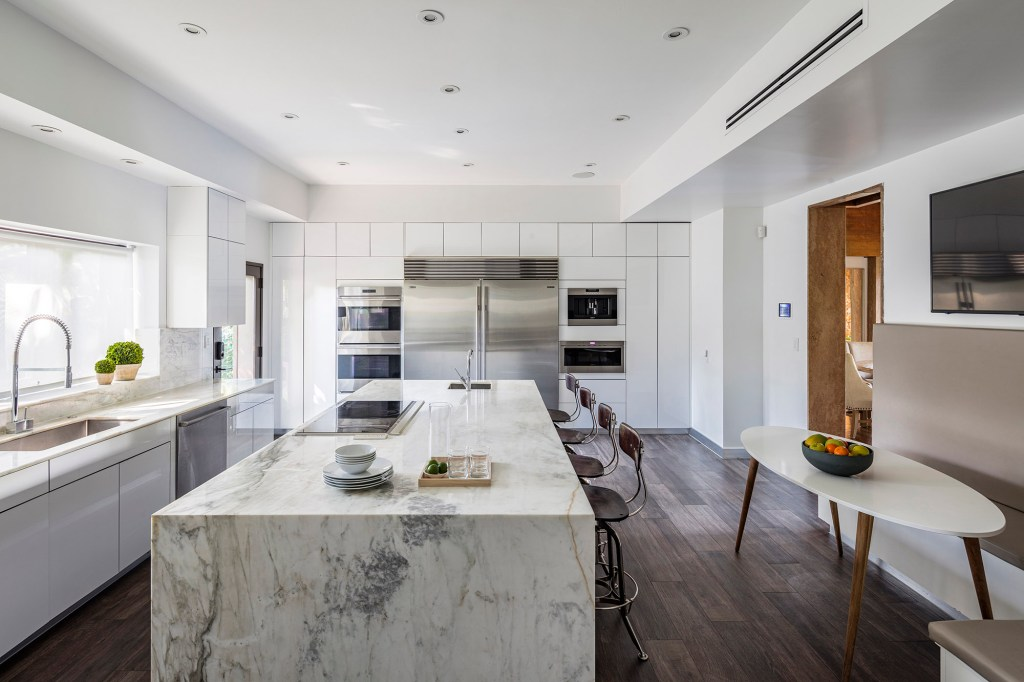 A white marble kitchen is pictured in the Miami house.