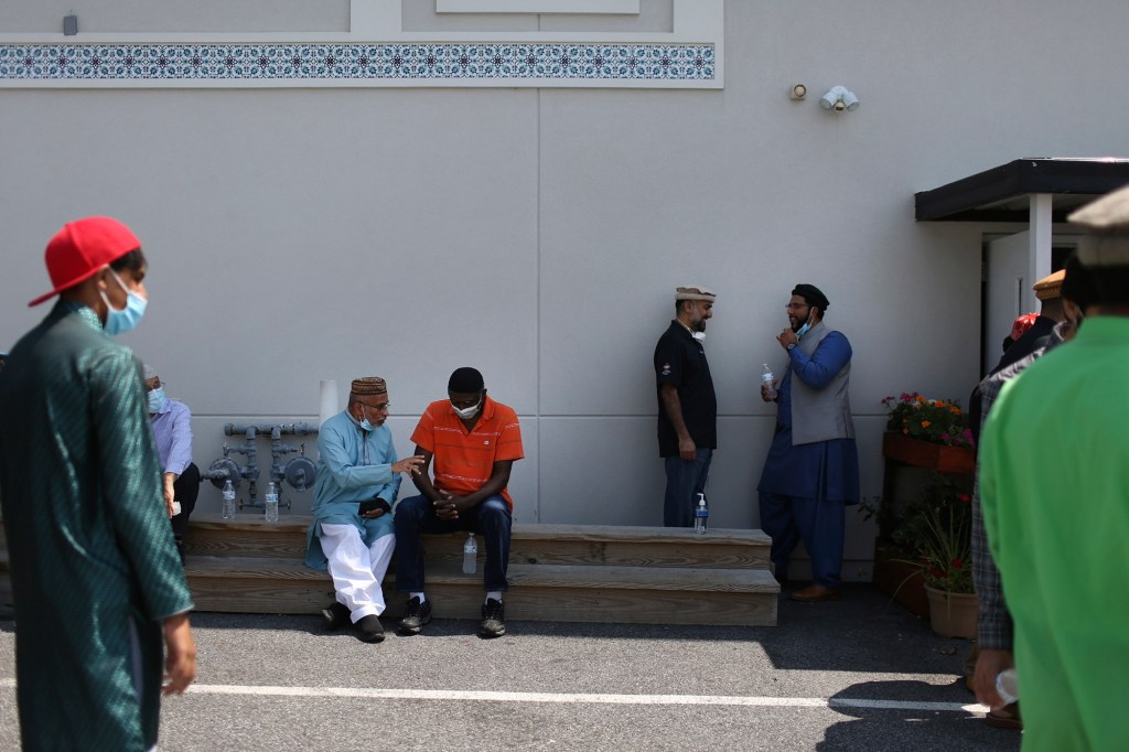 Community members talk outside of their local mosque in Rosedale, Md., after Friday prayer on Aug. 13, 2021.