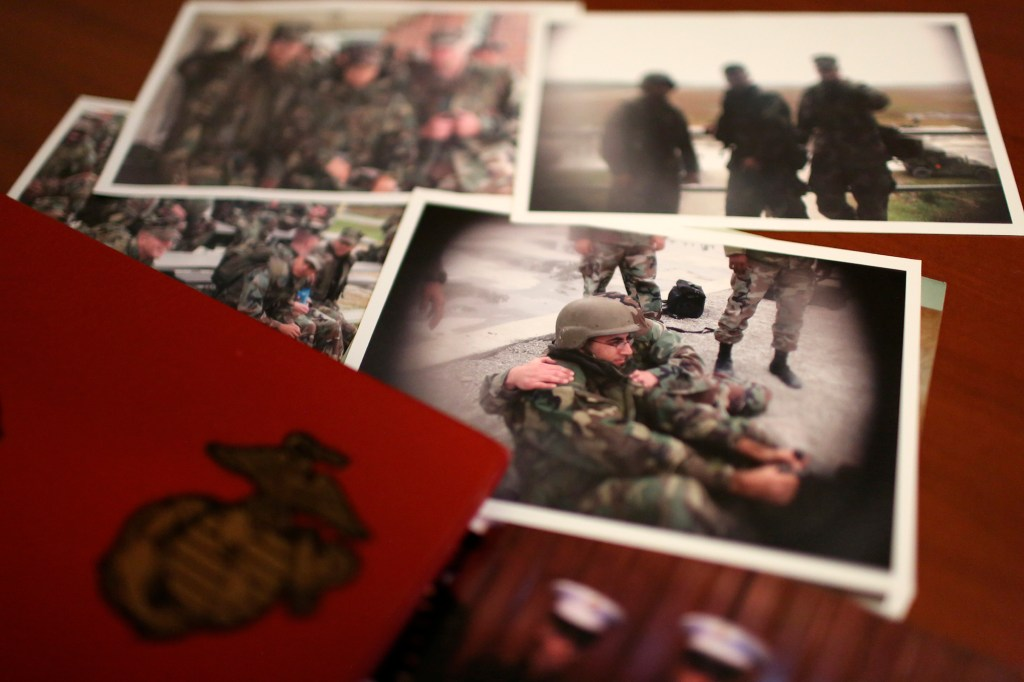 """A group of old photos laying on Mansoor Shams' desk in his Baltimore home on Friday, Aug. 13, 2021, show him as a young Marine during his service from 2000-2004. After 9/11, Shams was called names like """"Taliban,"""" """"terrorist"""" and """"Osama bin Laden"""" by some of his fellow Marines."""