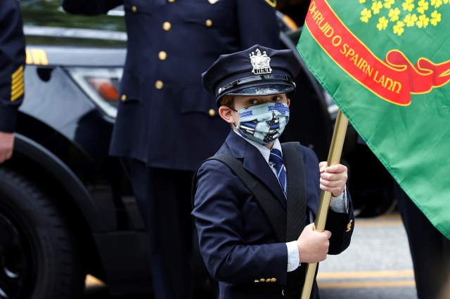 10-year-old Gavin Roberts wears his father's police hat as he carries a flag in the funeral procession of his father.