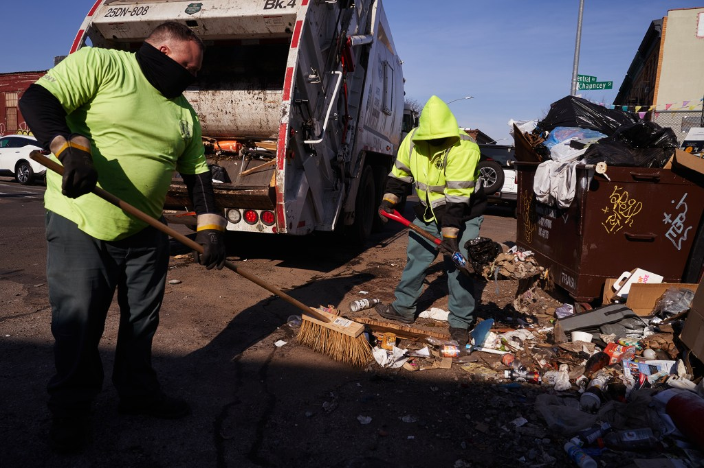 Sanitation Department workers collect garbage near 675 Central Avenue in Brooklyn on March 10, 2021.