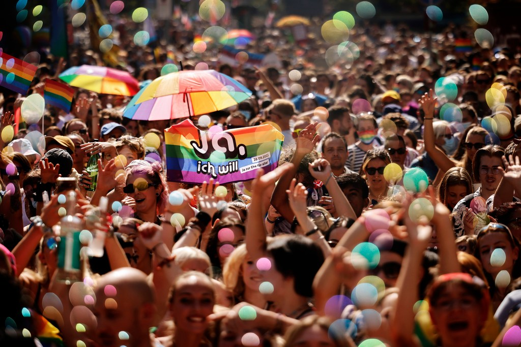 """In this Saturday, Sept. 4, 2021 file photo, people take part in the Zurich Pride parade in Zurich, Switzerland, with the slogan """"Dare. Marriage for all, now!"""" (Trau Dich. Ehe fuer alle. Jetzt!) for the rights of the LGBTIQ community."""
