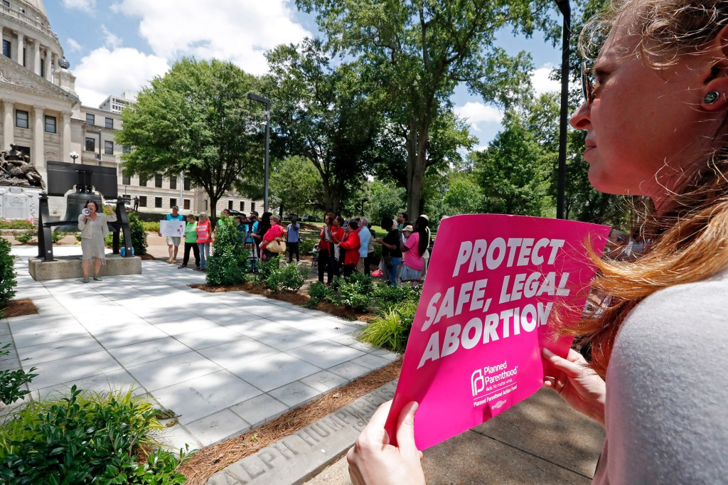 In this Tuesday, May 21, 2019 file photo, An abortion rights advocate holds a sign at the Capitol in Jackson, Miss. Republican lawmakers in at least a half dozen GOP-controlled states already are talking about copying a Texas law that bans abortions after a fetal heartbeat is detected.