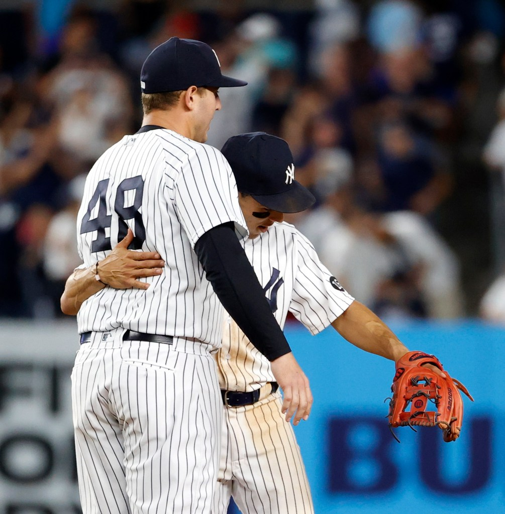 Yankees shortstop Andrew Velazquez, right, hugs Anthony Rizzo after the final out against the Boston Red Sox.
