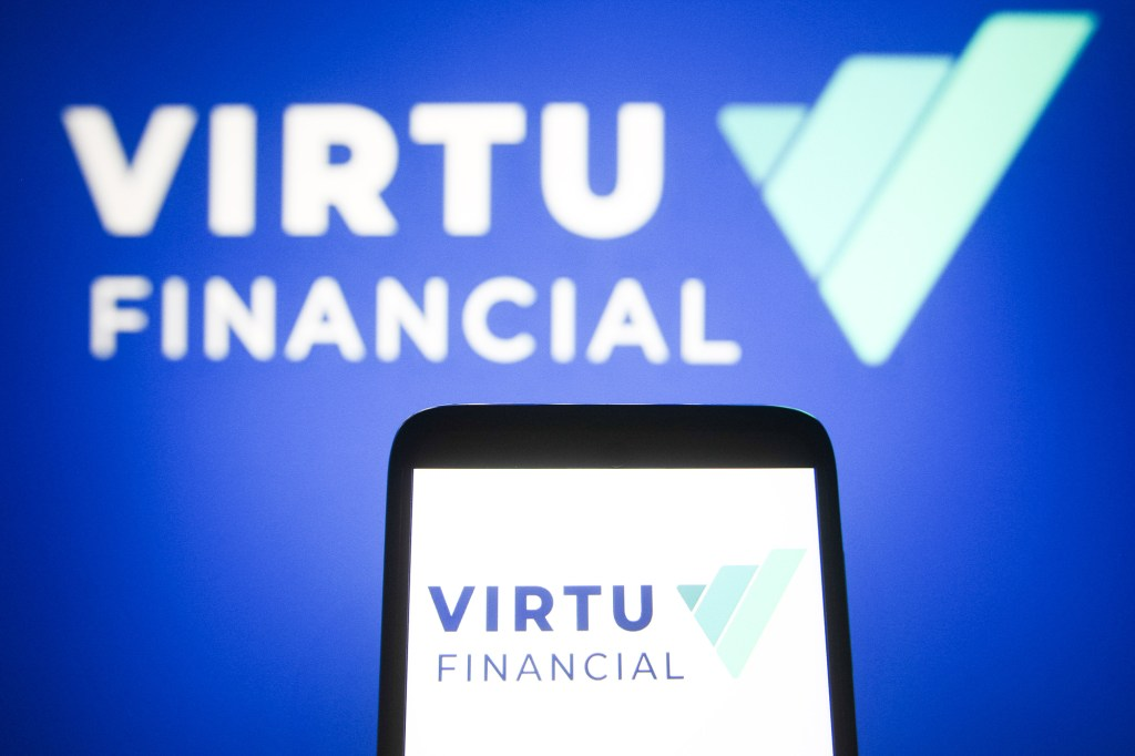 In this photo illustration, Virtu Financial logo is seen on a smartphone and a pc screen.