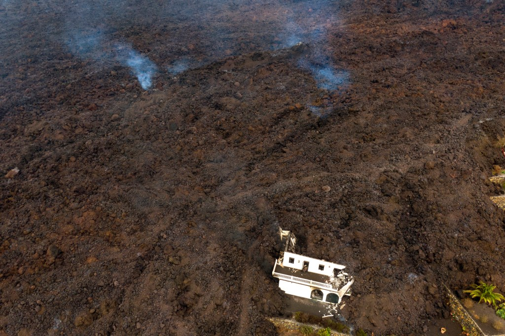 In this Tuesday, Sept. 21, 2021 file photo, lava from a volcano eruption flows destroying houses on the island of La Palma in the Canaries, Spain.