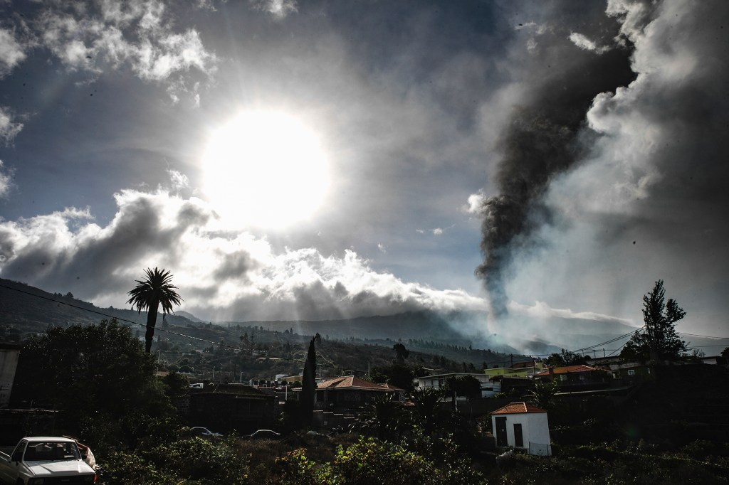 Smoke billows from a volcano near Los Llanos de Ariadne on the island of La Palma in the Canaries, Spain, Tuesday Sept. 21, 2021.