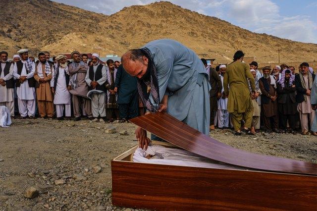 A man bids a respectful farewell to Zemari Ahmadi in his casket during a mass funeral.