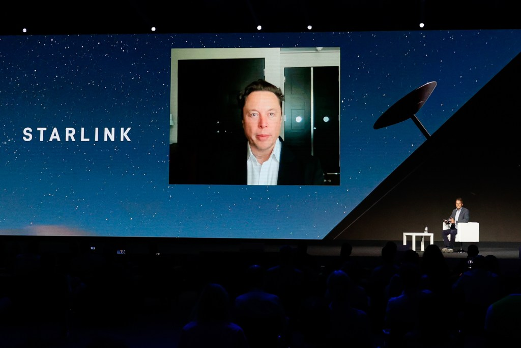 Elon Musk seen on a screen mounted on a stage at a conference