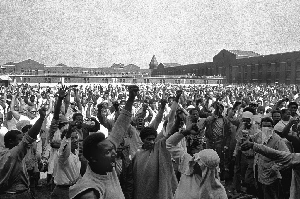 Inmates of Attica State Prison as they raise their hands in clenched fist salutes to voice their demands during a negotiating session with New York's prison Commissioner Russell Oswald.