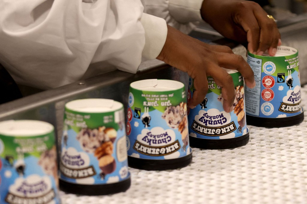 A worker places cartons of Ben & Jerry's ice cream upside down.