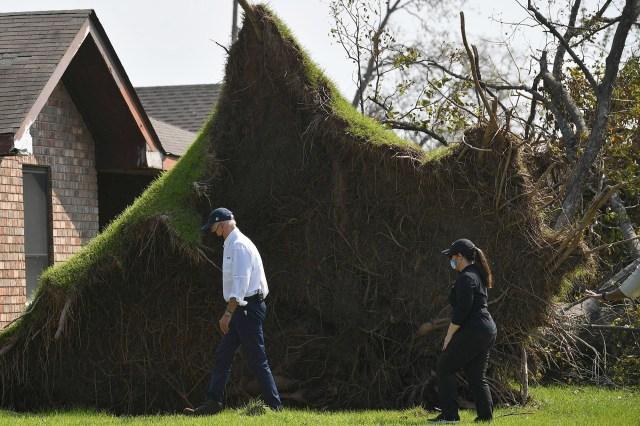 President Joe Biden walks by a tree uprooted during Hurricane Ida during his tour through the Cambridge neighbourhood in LaPlace, Louisiana.