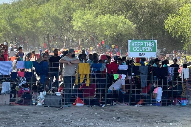 Migrants stand by the International Bridge in Del Rio, Texas.