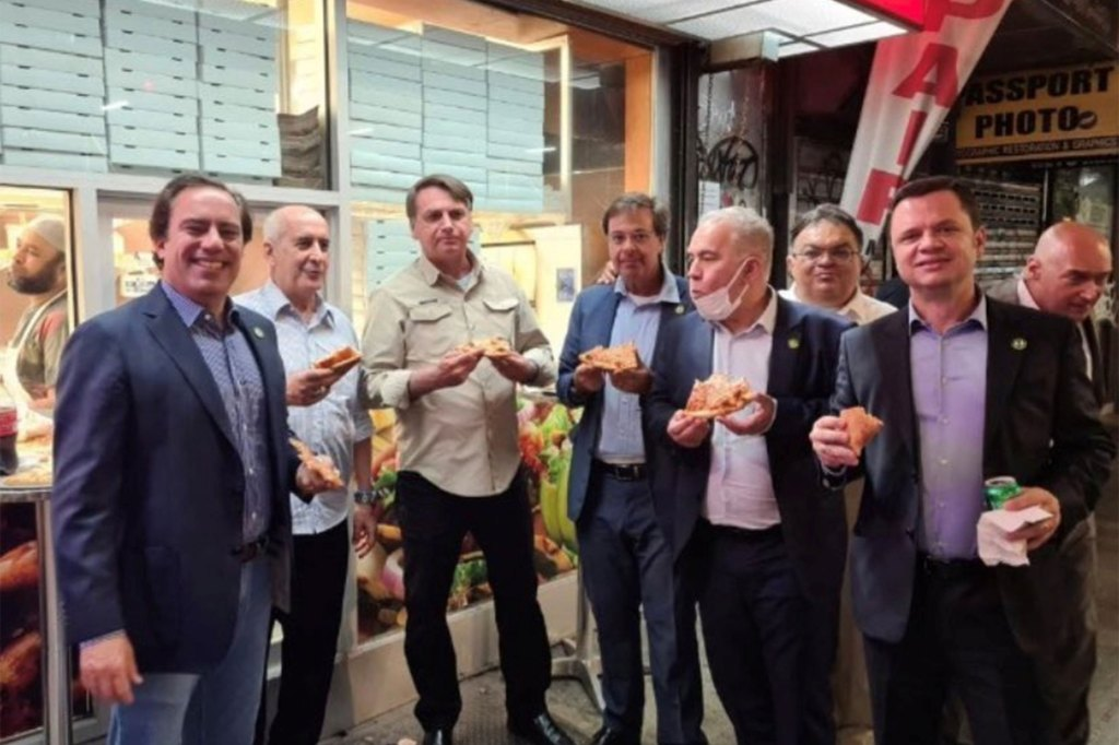Brazil's President Jair Bolsonaro (center in gold shirt), grabs a slice of pizza with the rest of the Brazilian delegation.
